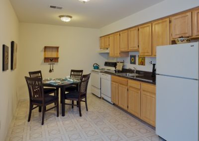 Kitchen in Apartment in South Jersey with wooden cabinets and white appliances.