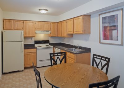 Kitchen in West Deptford, NJ Apartment with wooden cabinets and white appliances.