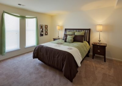 Furnished bedroom in West Deptford, NJ apartment with bed and two nightstands.